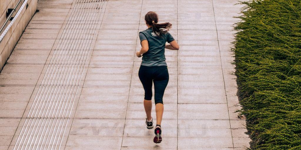 女性がランニングコースを走っている