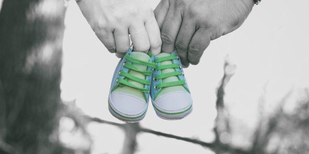 小さな子供の靴を持っているカップル