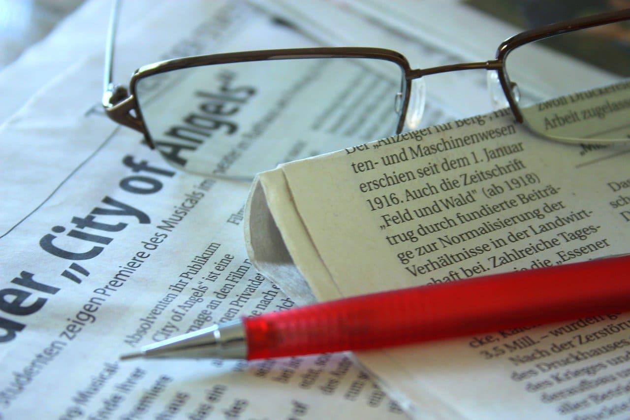 新聞と眼鏡とペンが置いてある