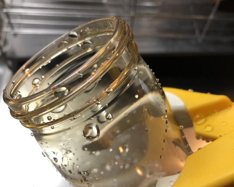 ミルトンの消毒液から取り出した濡れた哺乳瓶をトングで挟んでいる