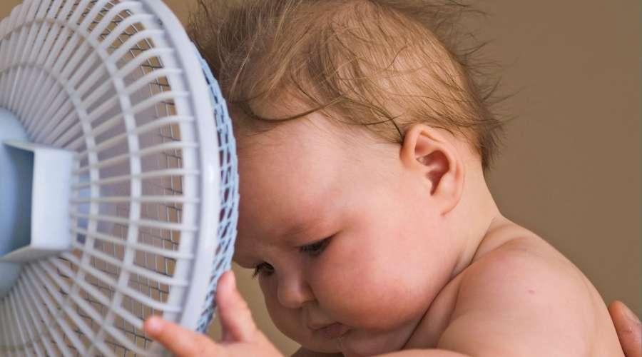 赤ちゃんが扇風機を触って、自分の方に向けている