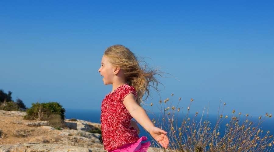 少女が海辺でそよ風を浴びている