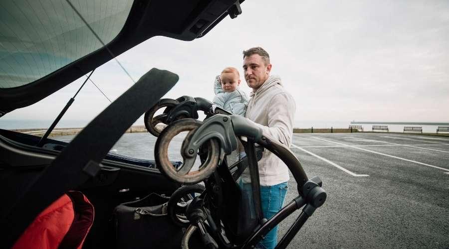 男性がベビーカーを車のトランクに入れている