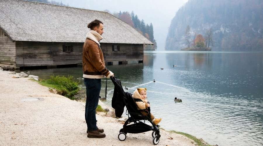 ベビーカーを押している男性が気持ちよさそうに湖を眺めている。