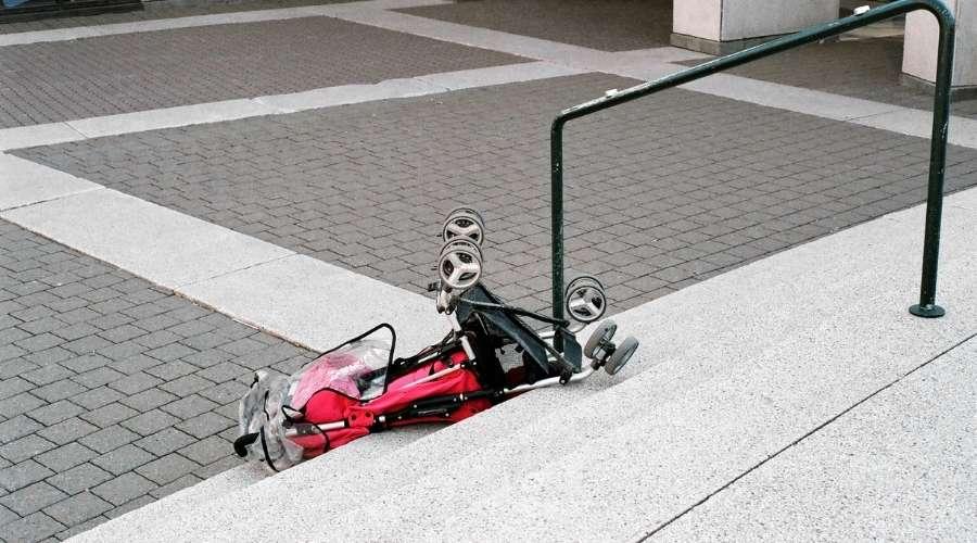 転倒している赤のベビーカーがある