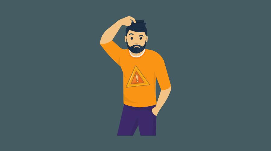 ハザードマークの書かれたTシャツを着た男性が、頭を掻いている。