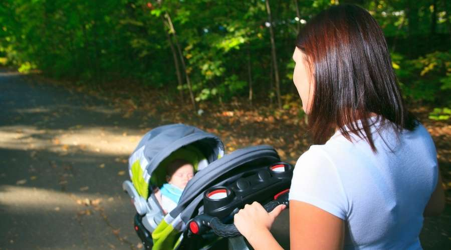 赤ちゃんが乗っているベビーカーを押している女性がいる