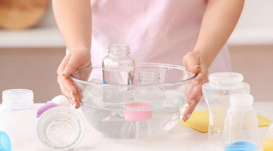 女性が哺乳瓶を消毒液につけている。
