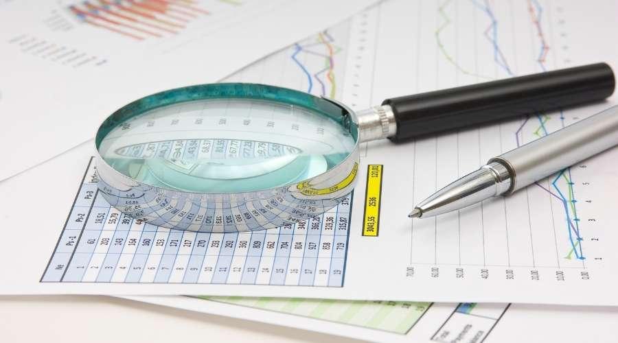データをまとめた表と虫眼鏡が置いてある。