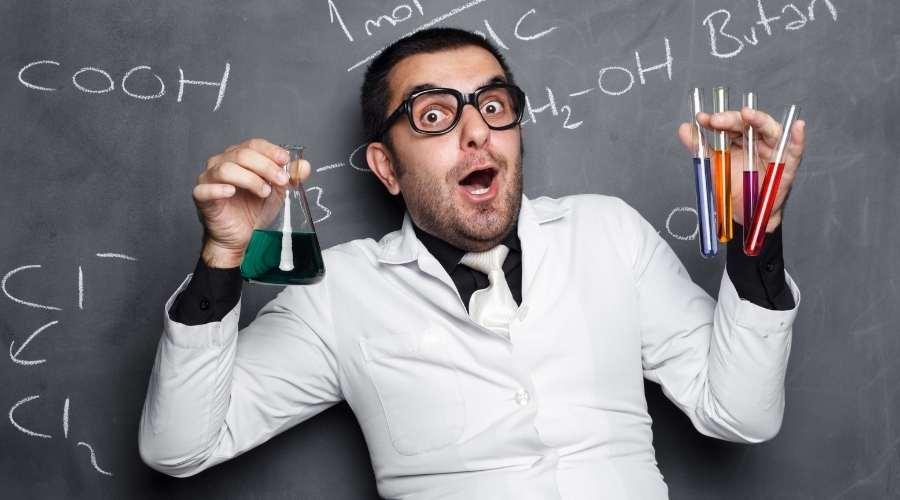 白衣を着た男性が、液体の入ったフラスコを持って実験している。