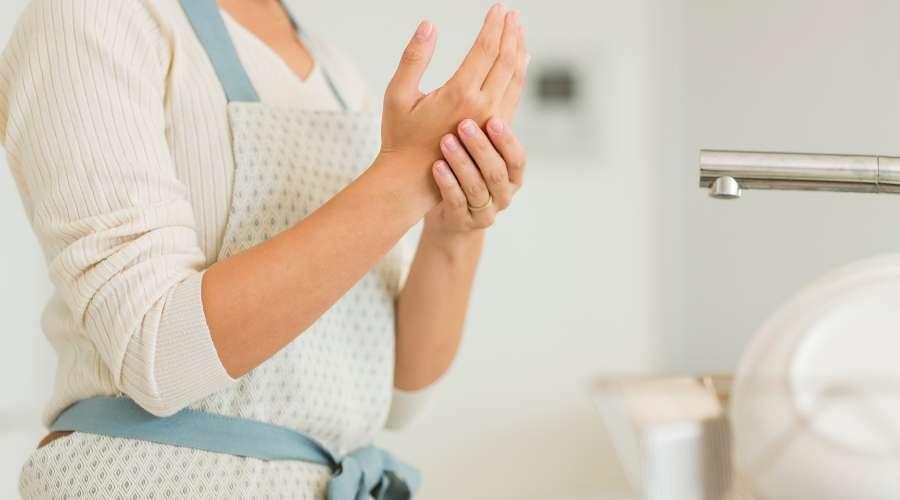 主婦が荒れた手をさすっている。