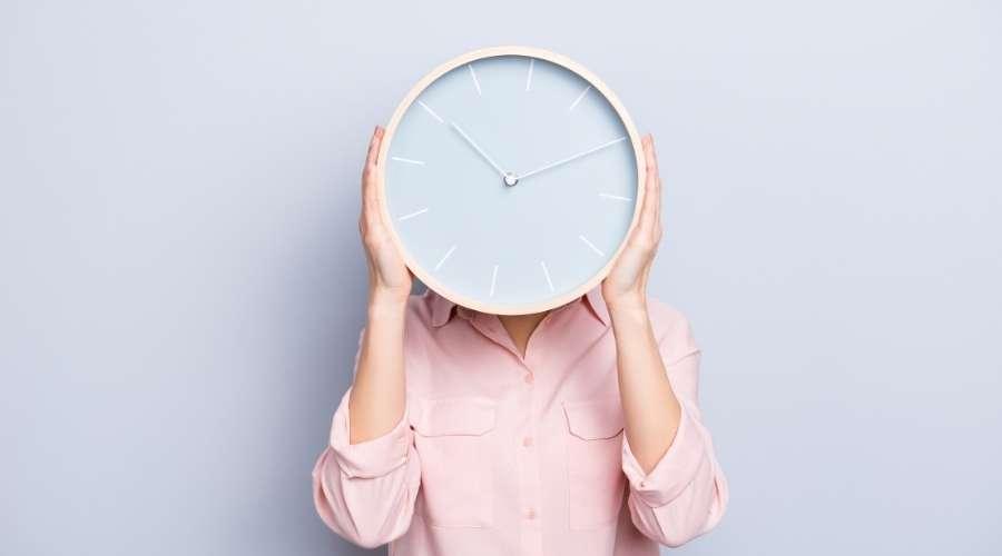 壁掛け時計を掲げた女性が立っている