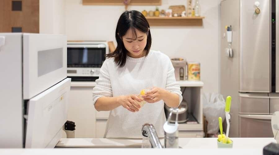 女性が哺乳瓶を消毒する準備をしている