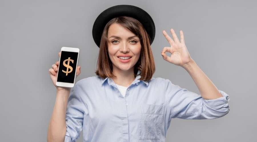 ドルマークの画面になっているスマートホンを、女性が持っている。そして左手でOKサインを出している