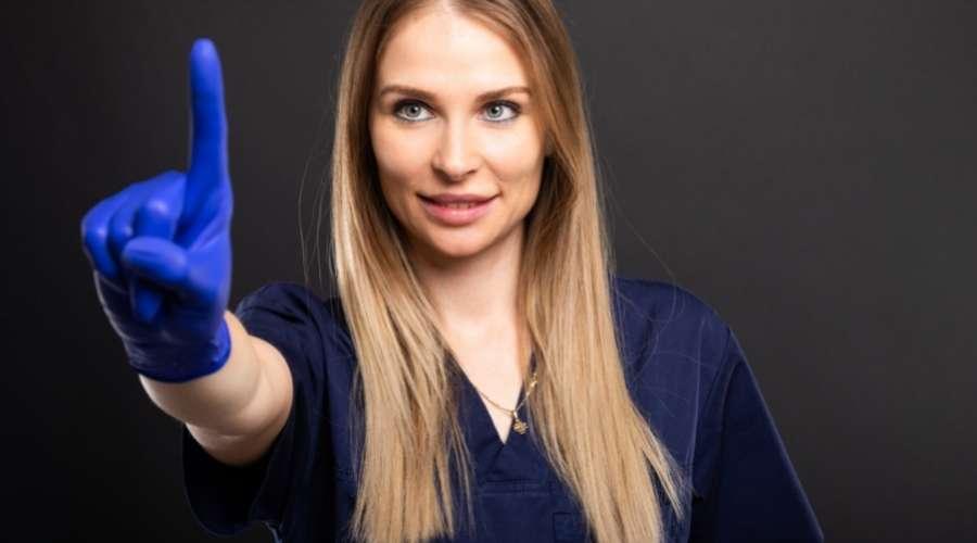 ゴム手袋を履いて、人差し指を立てている女性