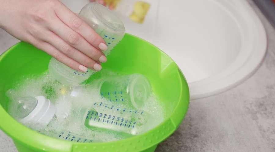 女性が哺乳瓶を洗剤で洗っている。